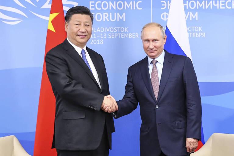 Com as bandeiras dos países atrás, Xi Jinping cumprimenta Vladimir Putin após encontro em Vladivostok, na Rússia