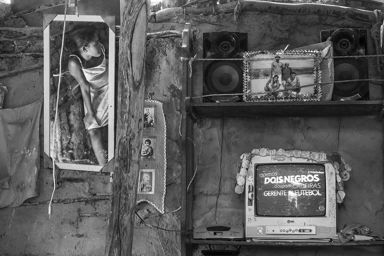 Interior de casa de pau a pique. A foto destaca uma das paredes da casa, que tem uma televisão e uma prateleira com fotos e caixa de som. Ao lado, um espelho também está pendurado na parede e reflete uma mulher sentada no chão