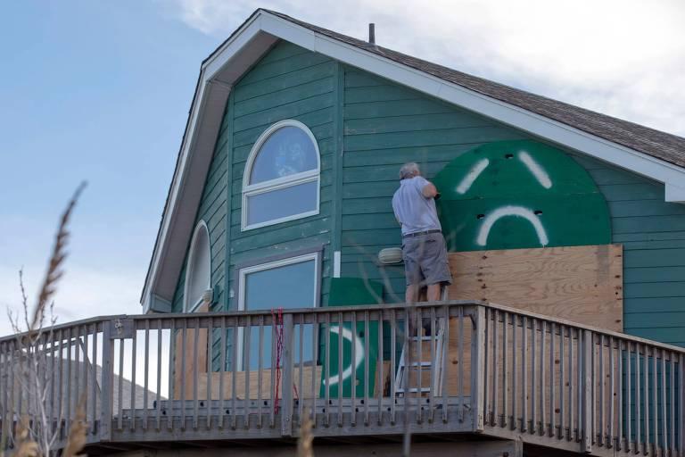 Homem está em uma escada instalando um pedaço de madeira verde em sua casa.