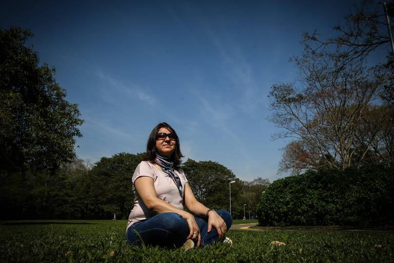 Glaucia Silva, 41, que usa serviço de coach oncológico durante seu tratamento, está sentada em um parque, em meio ao sol