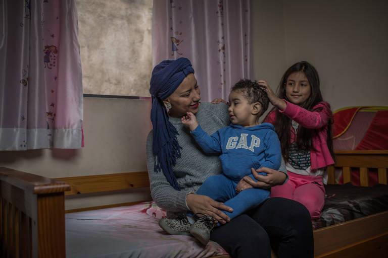 A assistente Regiane da Silva, 26, e seus filhos, Cauã, 1, e Gabrielle, 8, em casa, na zona norte de SP