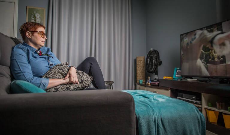 A cabeleireira Cíntia Gonçales, 38, assiste a programa de televisão na sua casa, em Guarulhos, na Grande São PauloBruno Santos/Folhapress