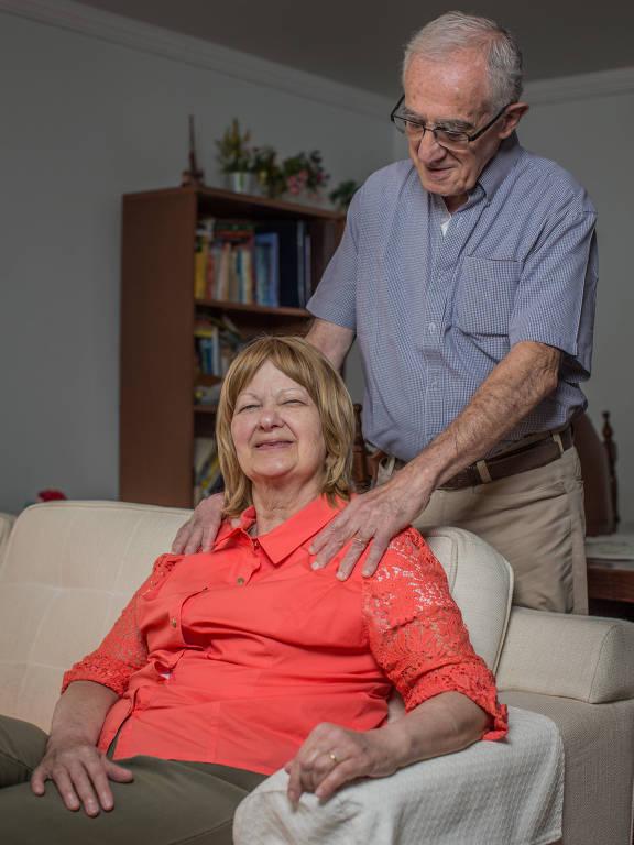 Idosa sentada em poltrona sorri para a foto, com idoso em pé atrás dela, com as mãos em seu ombro