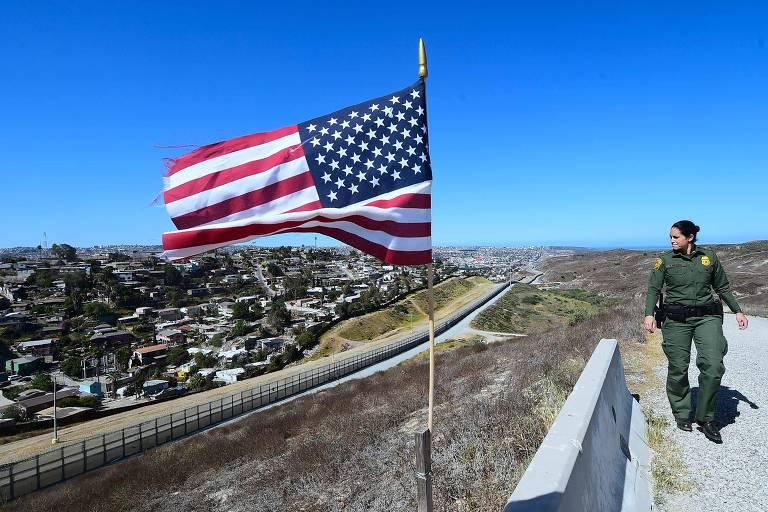Mulher com uniforme verde aparece do lado direito da imagem. No centro, há uma bandeira dos EUA em uma mureta que divide de uma área descampada que termina em uma grade do lado mexicano, em que há diversas casas.