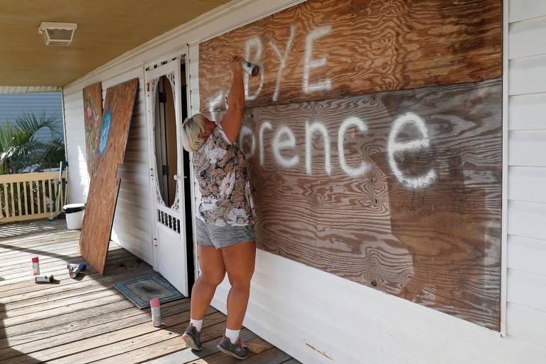 Mulher usa spray de tinta para escrever a expressão na placa de compensado. Ao lado, outras duas placas cobrem uma janela e uma porta.