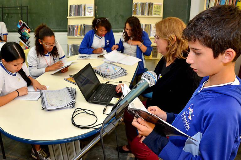 aluno em frente ao microfone se prepara para narrar uma história ao lado da professora e colegas em uma sala de leitura