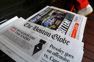 FILE PHOTO: The front page of the Boston Globe newspaper references their editorial defense of press freedom at a newsstand in Cambridge