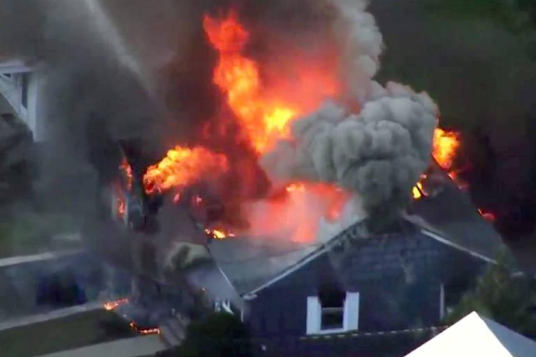 Casa cinza com janelas brancas aparece com o telhado pegando fogo.