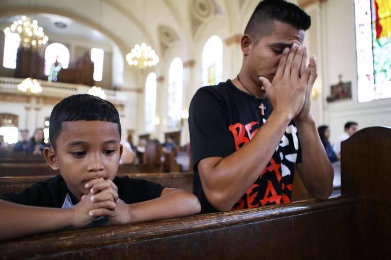 Homem e menino juntam as mãos enquanto ajoelham no genuflexório da igreja