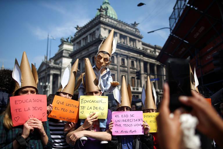 Boneco de Macri aparece com chapéu de burro, acima de professoras que usam o adereço e carregam cartazes coloridos com a mesma frase.
