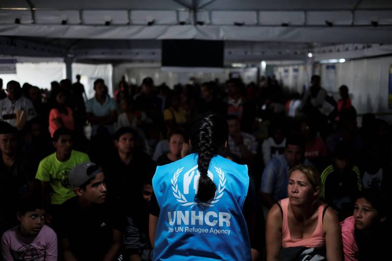 Mulher aparece de costas com colete azul com o símbolo do Acnur, enquanto é observada por outras pessoas. Eles estão em uma tenda branca.