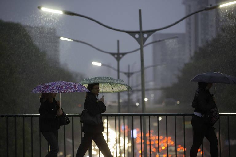 Pessoas caminham sob forte chuva no viaduto Santa Generosa, região central da capital paulista, na manhã desta sexta (14).