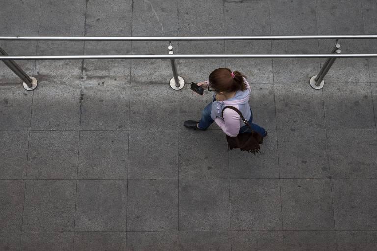 Mulher usa celular próximo à estação Anhangabaú