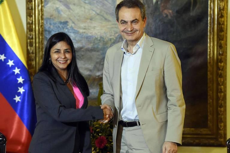 Delcy Rodriguez, à esquerda, sorri para a câmera enquanto aperta a mão de josé luiz rodriguez zapatero, que também encara a câmera; atrás dos dois há um quadro e, ao lado dela, uma bandeira da Venezuela