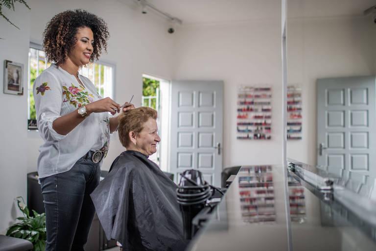 A cabeleireira Julyana Carvalho dos Santos, 29, em seu salão de beleza em Taboão da Serra