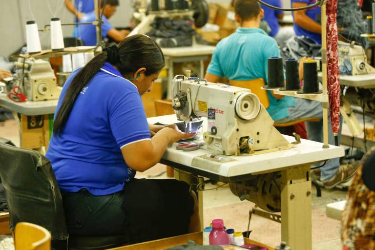 Mulher trabalha em máquina de costura