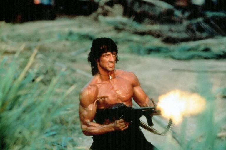 Rambo aparece sem camisa, musculoso, disparando uma metralhadora