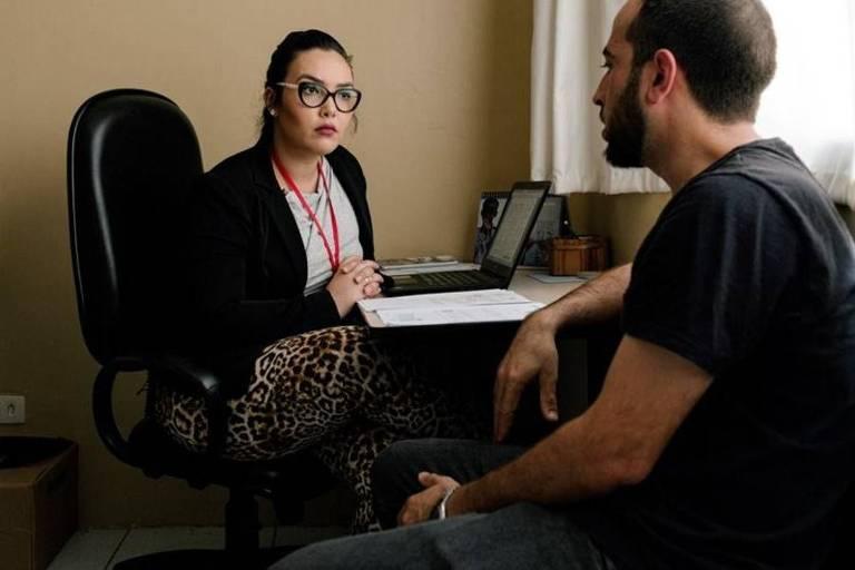 Camila, sentada à uma mesa com uma estante de livros atrás, conversa com um homem sentado e faz anotações