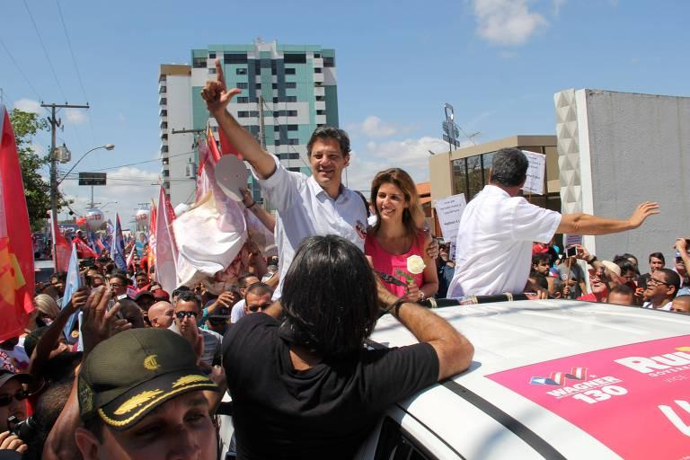 """O presidenciável Fernando Haddad  (PT) em campanha em Vitória da Conquista, na Bahia. Ele acena com um gesto em que o polegar e o indicador formam a letra """"L"""", em cima da caçamba de uma caminhonete branca, ao lado de sua esposa, Ana Estela"""