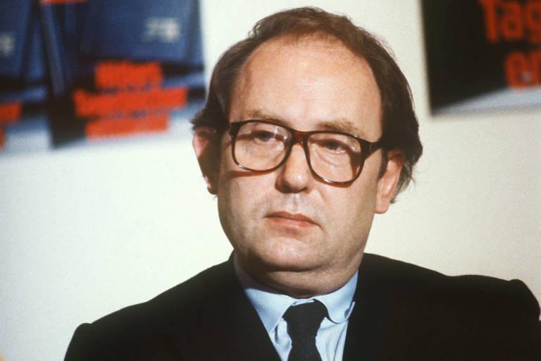 Gerd Heidemann , sentado e de terno, cruza os braços durante entrevista; ao fundo, poster com a capa da revista Stern fora de foco