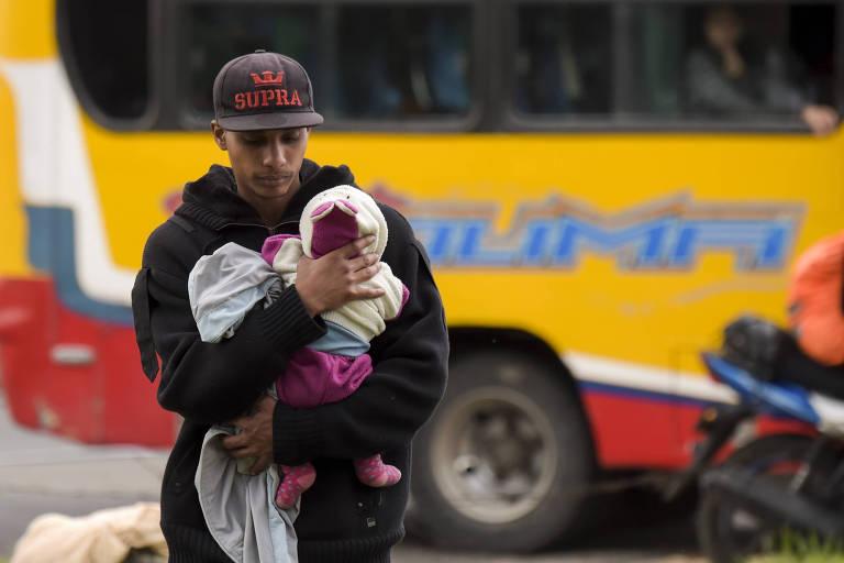 Homem de boné carrega um bebê distanciando-se de um ônibus amarelo