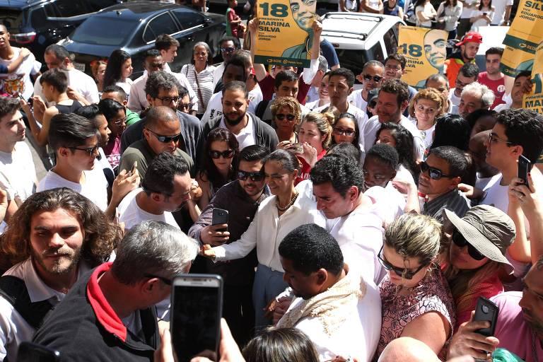Cordão de segurança é formado em torno de Marina Silva durante caminhada pela rua 25 de Março, em São Paulo