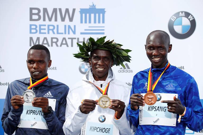 Eliud Kipchoge, no centro, posa ao lado de Amos Kipruto (à esquerda) e de Wilson Kipsang (à direita), no pódio da Maratona de Berlim