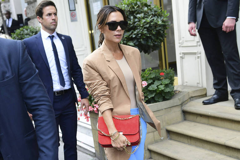 Victoria Beckham anda em uma rua ao lado de seguranças. Ela usa óculos escuros, veste calça jeans, blazer claro e segura uma bolsa vermelha