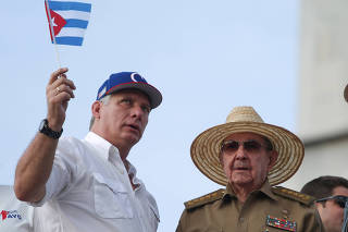 FILE PHOTO: Cuba's First Secretary of the Communist Party and former President Raul Castro speaks to Cuba's President Miguel Diaz-Canel as they watch the May Day rally in Havana