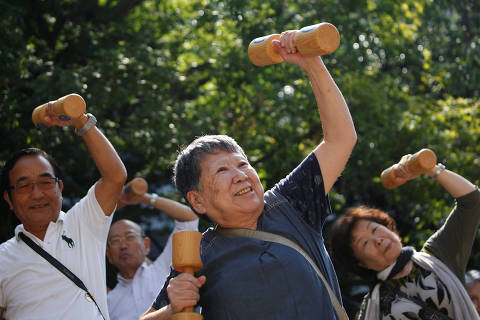 Elderly and middle-aged people exercise with wooden dumbbells during a health promotion event to mark Japan's