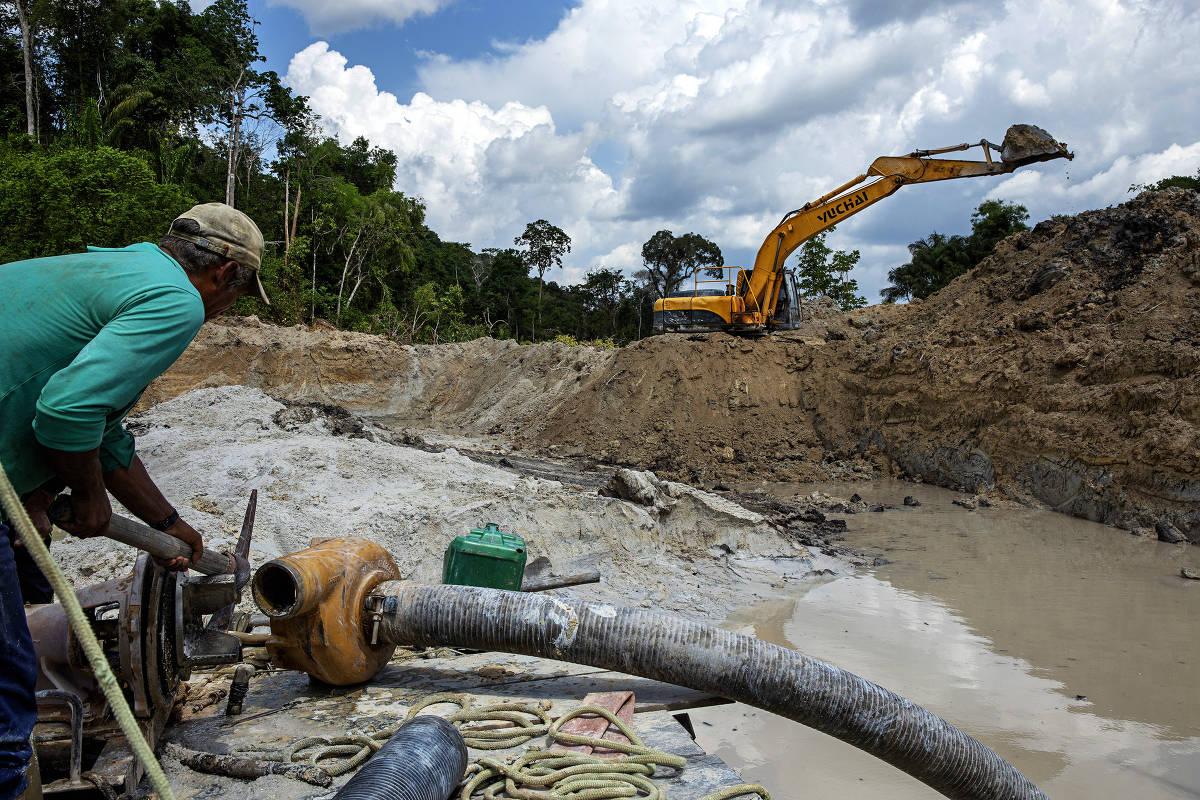 Escavadeira prepara o solo enquanto homem conserta bomba de água para ajudar no garimpo no rio Rato, afluente do rio Tapajós