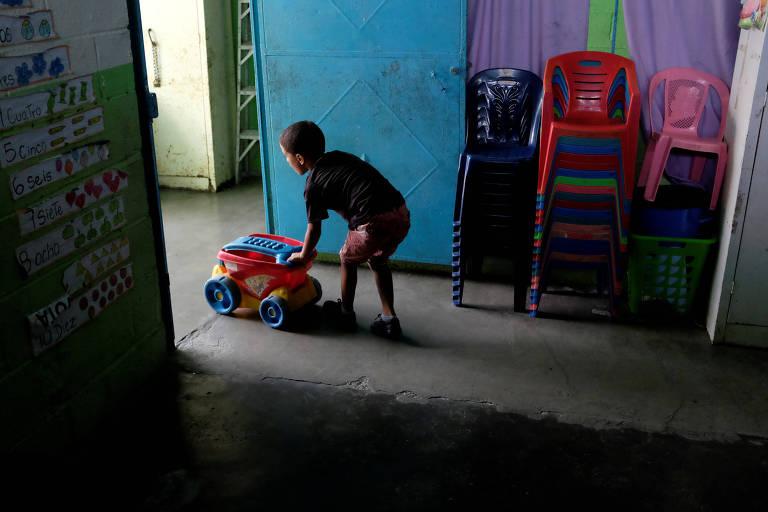 Menino aparece do lado da porta da escola, na cor azul. Ele empurra um carrinho colorido para fora da sala. À direita aparecem cadeiras de plástico coloridas empilhadas.