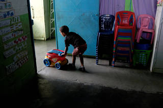 A kid pushes a toy cart next to a stack of chairs in a classroom on the first day of school, in Caucagua