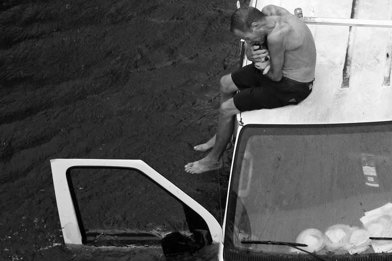 Com um cachorro no colo, homem aguarda resgate em Pollocksville, na Carolina do Norte (EUA)