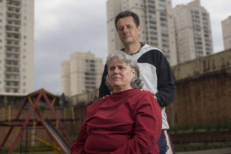 Marisa está sentada e José Valdir está em pé. Há um muro ao fundo e prédios no horizonte