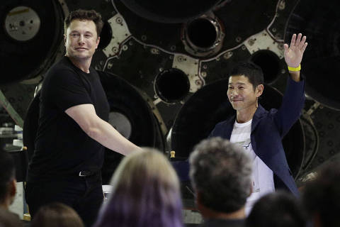 SpaceX founder and chief executive Elon Musk, left, shakes hands with Japanese billionaire Yusaku Maezawa, right, after announcing him as the first private passenger on a trip around the moon, Monday, Sept. 17, 2018, in Hawthorne, Calif. (AP Photo/Chris Carlson) ORG XMIT: CAJL116