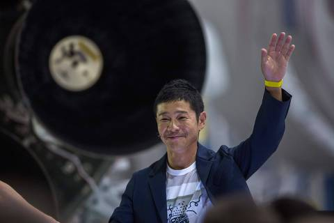 Japanese billionaire Yusaku Maezawa speaks near a Falcon 9 rocket during the announcement by Elon Musk to be the first private passenger who will fly around the Moon aboard the SpaceX BFR launch vehicle, at the SpaceX headquarters and rocket factory on September 17, 2018 in Hawthorne, California. - Japanese billionaire businessman, online fashion tycoon and art collector Yusaku Maezawa was revealed as the first tourist who will fly on a SpaceX rocket around the Moon. (Photo by DAVID MCNEW / AFP)