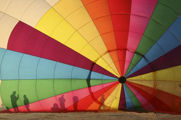Sombras de pessoas em frente a um balão colorido, durante festival no México