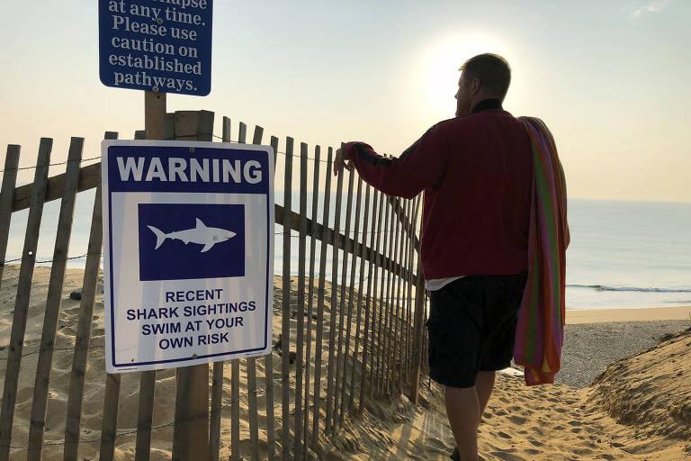 Placa de perigo avisa sobre o avistamento recente de tubarões em Cape Cod, Massachusetts, onde brasileiro foi morto por tubarão