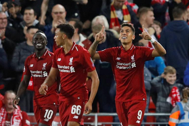 Firmino ergue as mãos para o alto e comemora o gol da vitória do gol do Liverpool em Anfield sobre o PSG