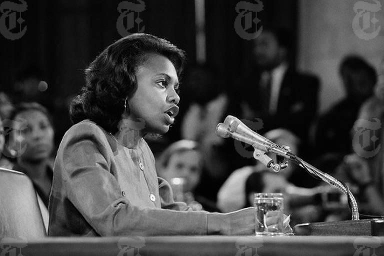 Foto em preto e branco mostra Anita Hill sentada em uma mesa, com pessoas em cadeiras próximas, falando a um microfone