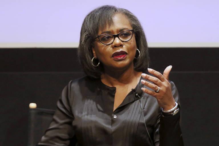 De camisa preta e óculos, Hill ergue a mão esquerda e fala como se explicando algo