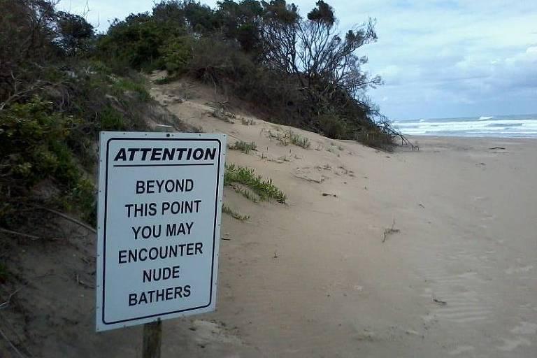 Placa alerta visitantes sobre a possibilidade de que encontrem pessoas nuas na praia de Mpenjati, na África no Sul