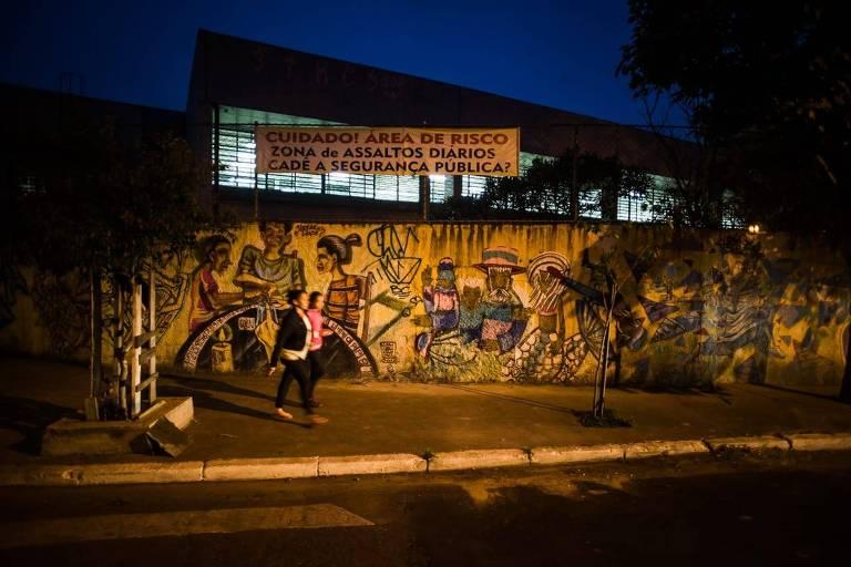 """Imagem mostra muro grafitado com faixa onde se lê """"Cuidado! Área de risco, zona de assaltos diários. Cadê a segurança pública?"""""""
