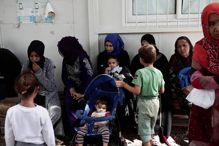 Sete mulheres, todas com véu islâmico, esperam sentadas. Da direita para a esquerda a primeira e a quarta carregam crianças de colo. À frente da terceira há um menino com roupas verdes e à frente da quarta há um carrinho de bebê. Uma quinta criança, uma menina, está à distância em frente à sexta.