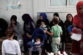 FILE PHOTO: Women and children sit at the Moria camp for refugees and migrants on the island of Lesbos