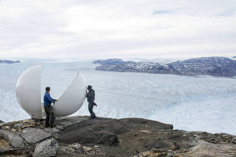 Safety officer Brian Rougeux works with student Febin Magar to assemble a radar dome while working in a science camp on the side of the Helheim glacier near Tasiilaq, Greenland, June 20, 2018. REUTERS/Lucas Jackson  SEARCH