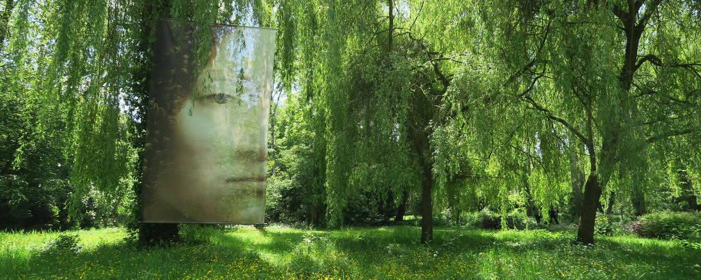 Quadro de Leonardo da Vinci reproduzido em tela translúcida no meio da vegetação dos jardins do castelo Clos Lucé, em Amboise
