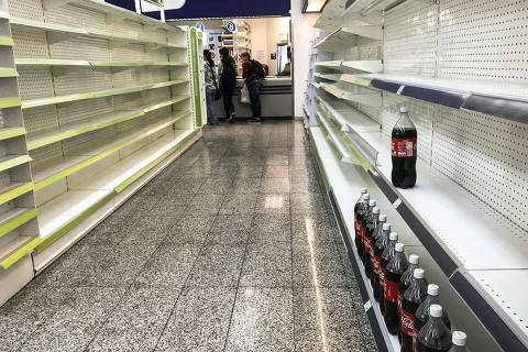 TOPSHOT - A few bottles of softdrink remain on the empty shelves of a supermarket in Caracas, on August 28, 2018. - Scarcity increases as Venezuela's government controls prices in commericial establishments in an atempt to curb hyperinflation. (Photo by RONALDO SCHEMIDT / AFP) ORG XMIT: RSA1601