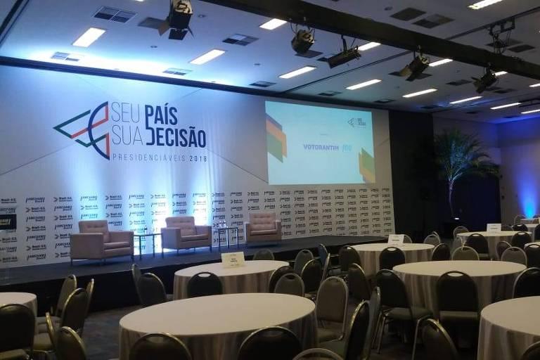 Mesas em plateia e palco de evento na Câmara Americana de Comércio em São Paulo